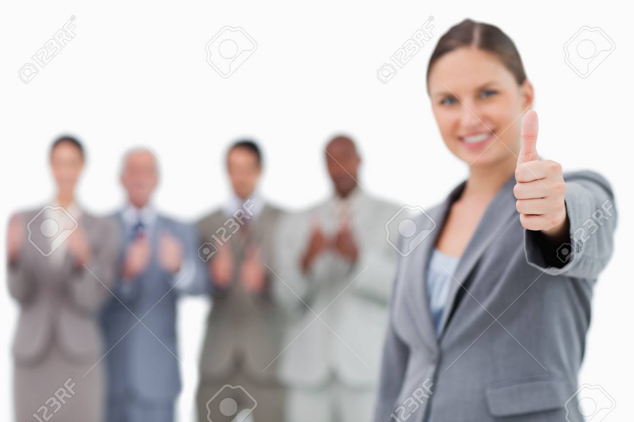 Smiling businesswoman with thumb up and colleagues behind her against a white background Stock Photo - 13606545