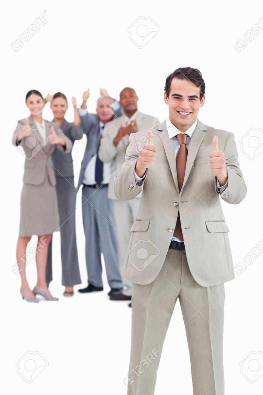 Smiling businessman with team behind him giving thumbs up against a white background Stock Photo - 13606594