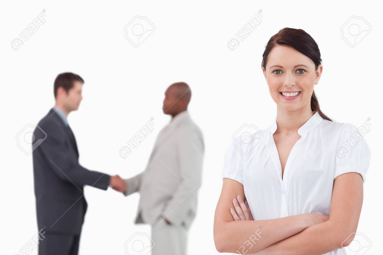 Businesswoman with arms folded and hand shaking trading partners behind her against a white background Stock Photo - 13603136