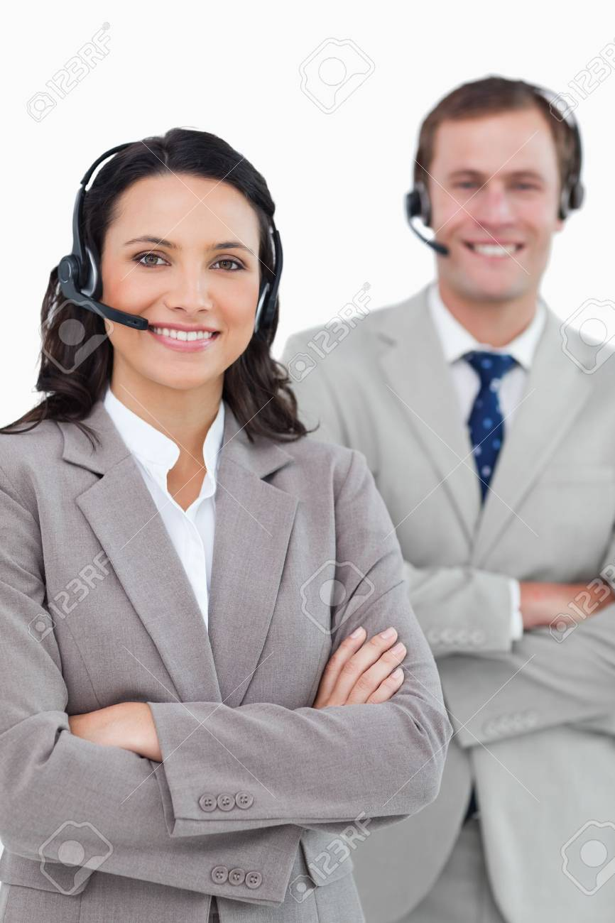 Smiling call center agents with headsets and arms folded against a white background Stock Photo - 13616487