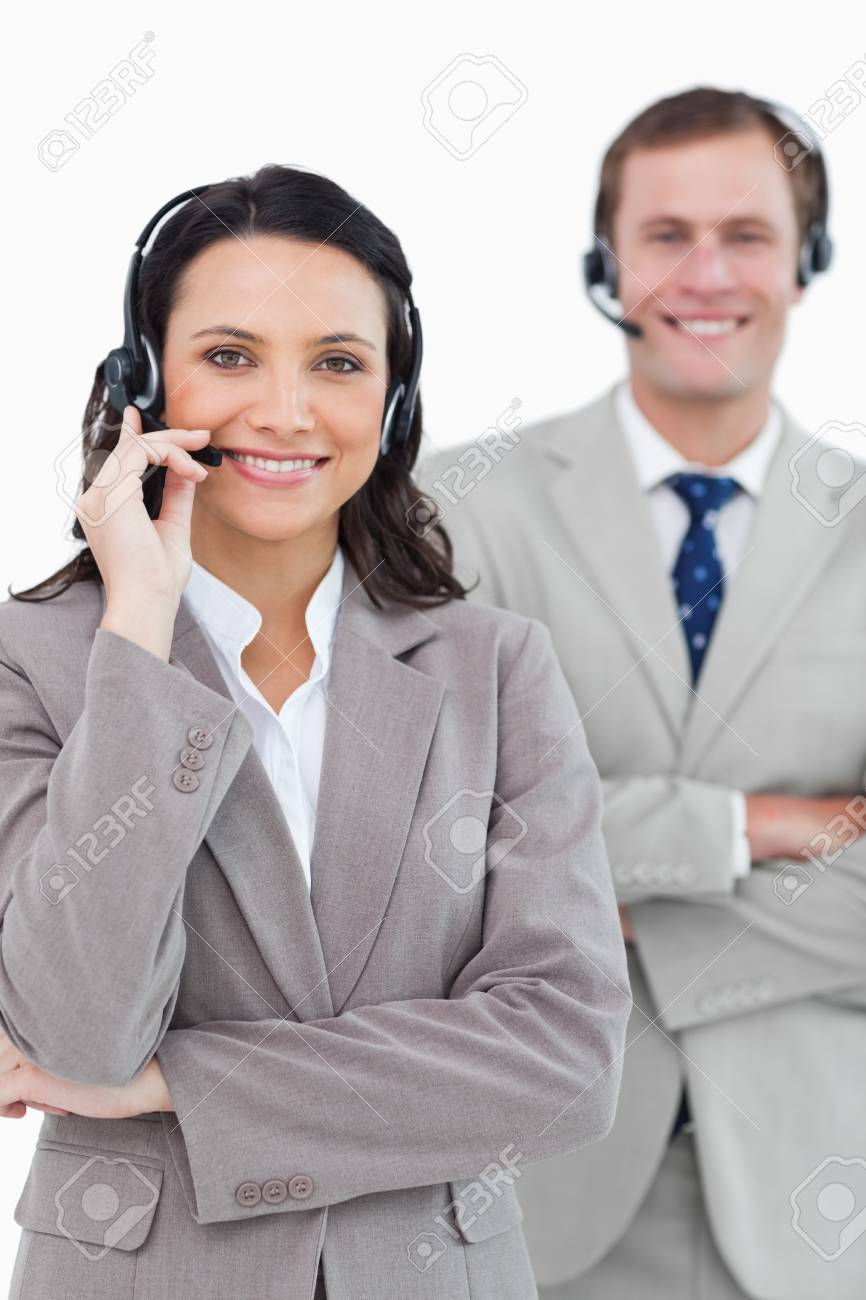 Smiling call center agents with headsets on and arms folded against a white background Stock Photo - 13616490