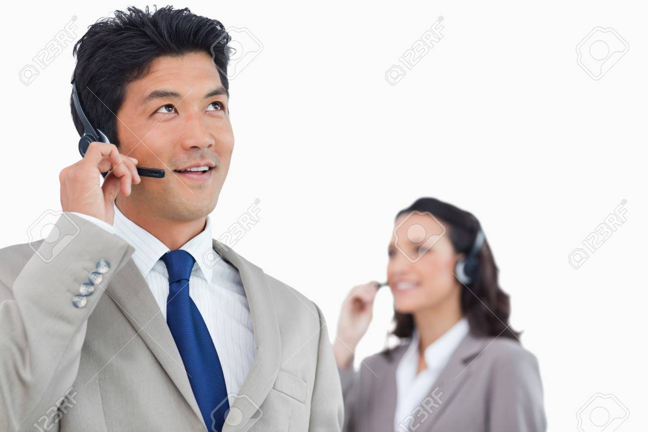 Call center agent with headset and colleague behind him against a white background Stock Photo - 13606754