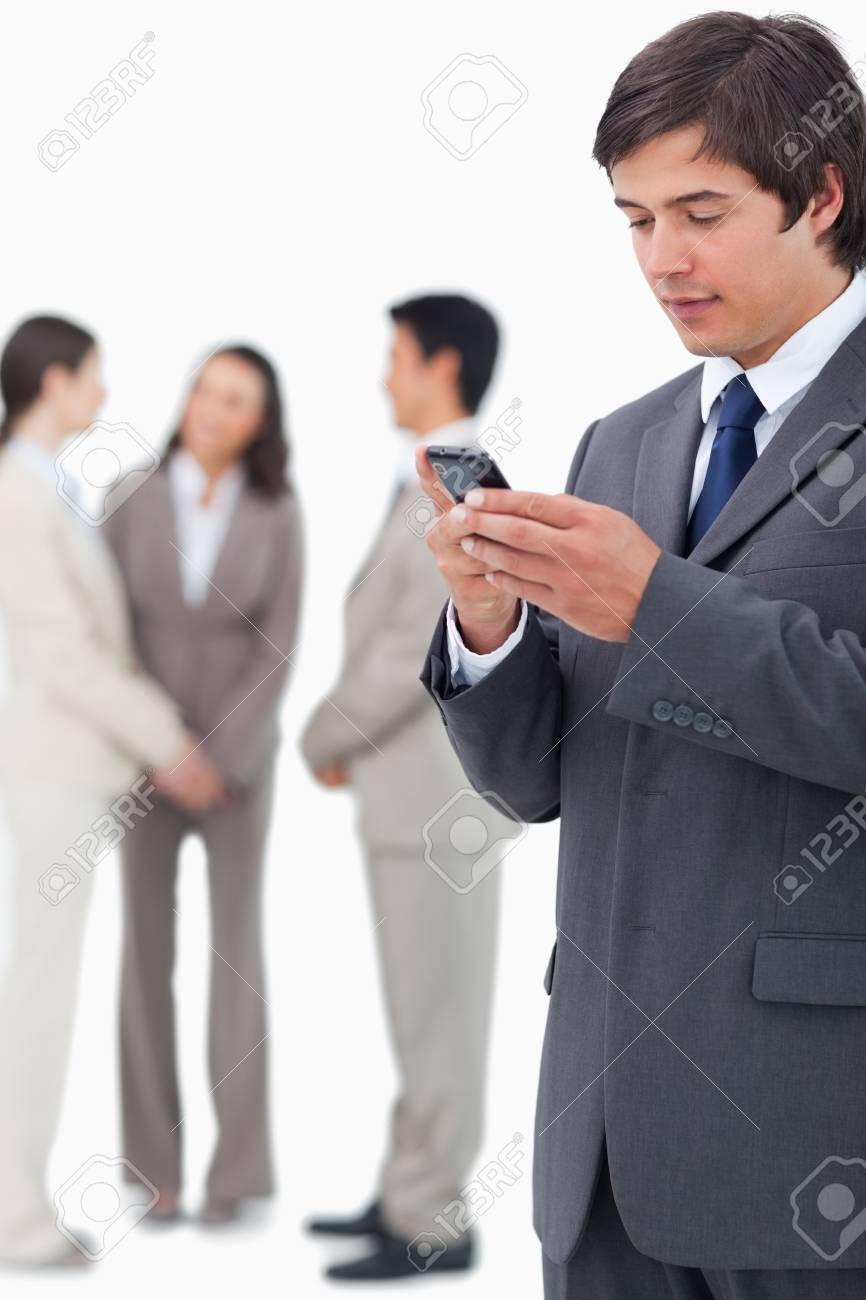 Salesman reading text message on cellphone with team behind him against a white background Stock Photo - 13616145
