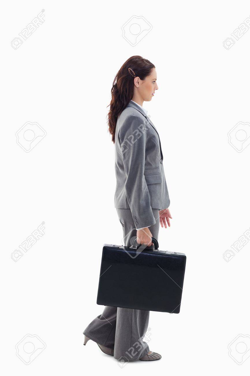 Profile of a businesswoman walking with a briefcase against white background Stock Photo - 13600540