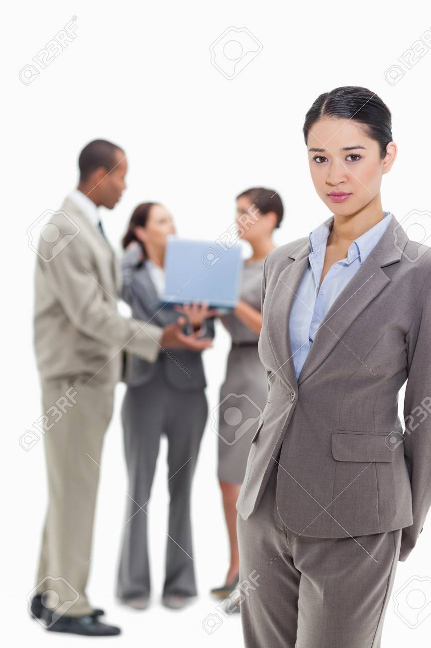 Serious businesswoman with co-workers talking with a laptop in the background Stock Photo - 13616305