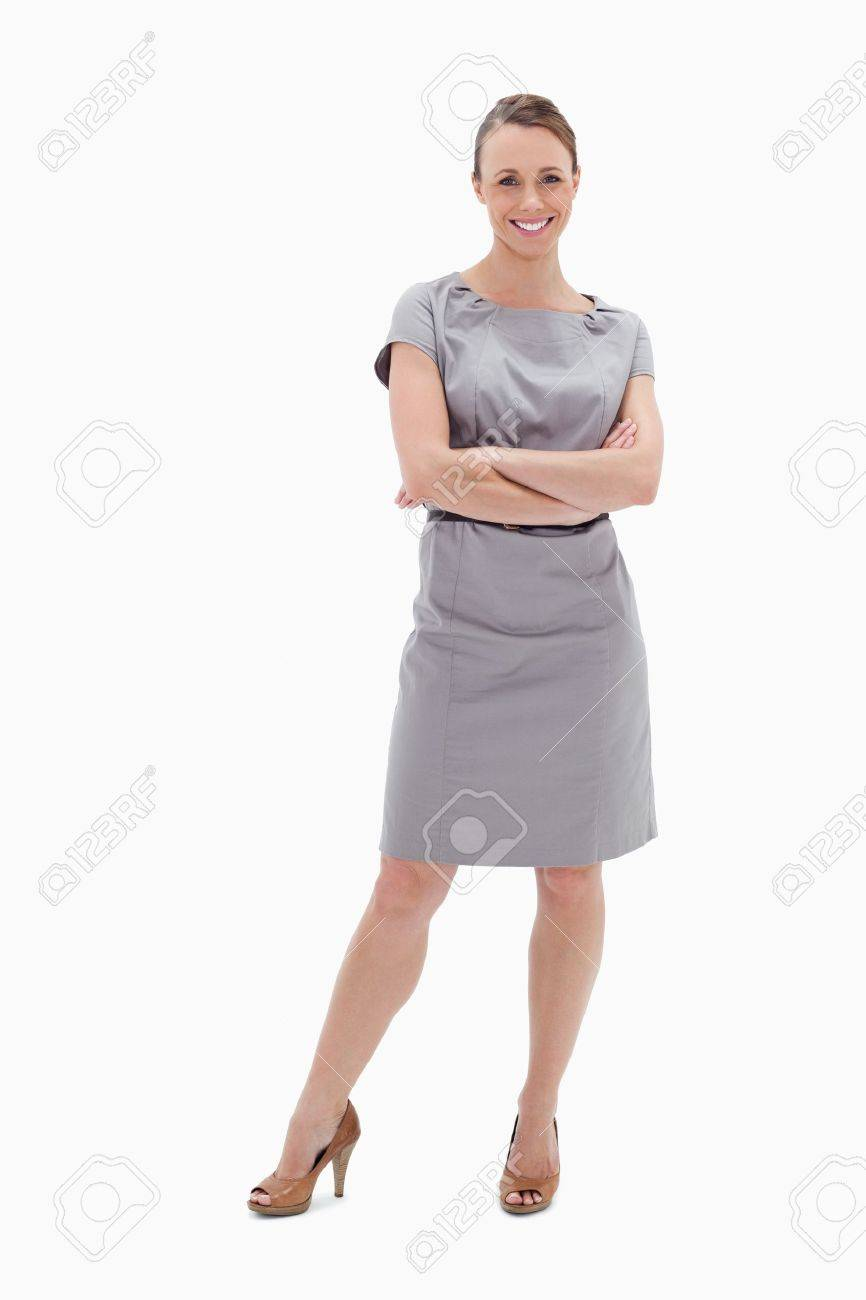 Smiling woman in dress with her arms folded against white background - 13600467