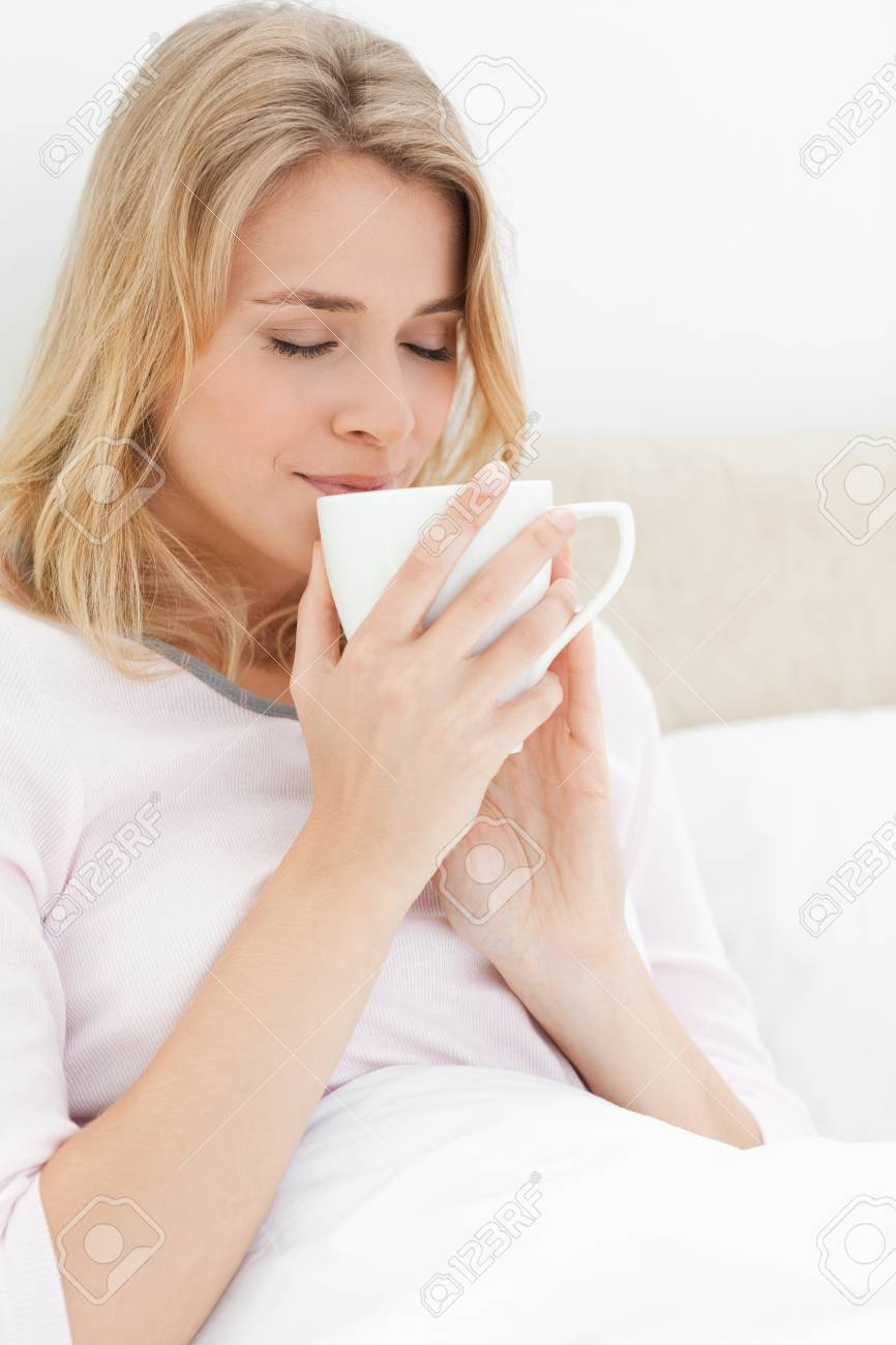 A close up shot of a woman holding a cup up to her face, with her eyes closed. Smelling the contents of the cup. Stock Photo - 13658981