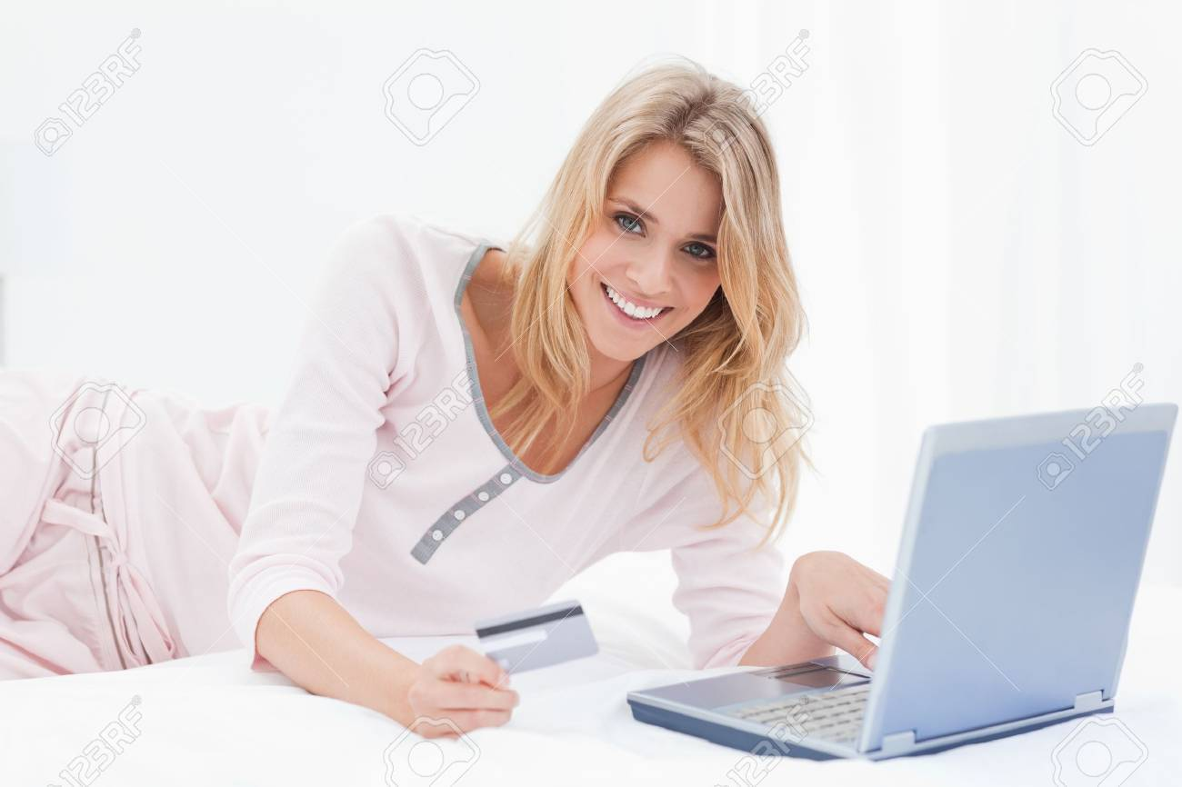 A woman is lying on the bed smiling as she looks forward while ordering items online with her laptop and credit card Stock Photo - 13650773