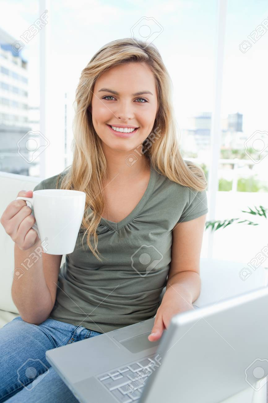 A woman smiles as she uses her laptop and holds a cup in her hand, all while looking in front of her. Stock Photo - 13673842