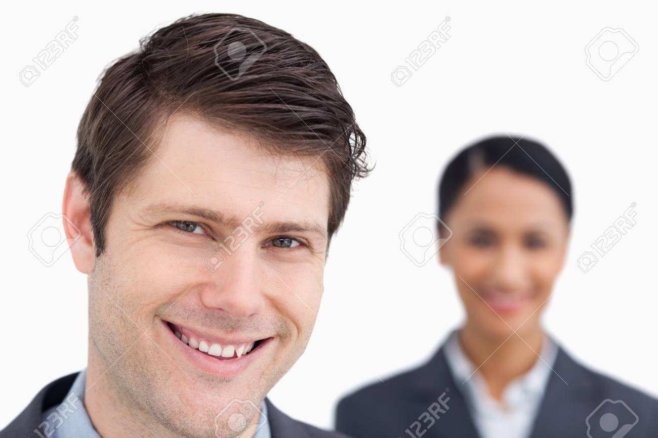 Close up of smiling salesman with colleague behind him against a white background Stock Photo - 18681562