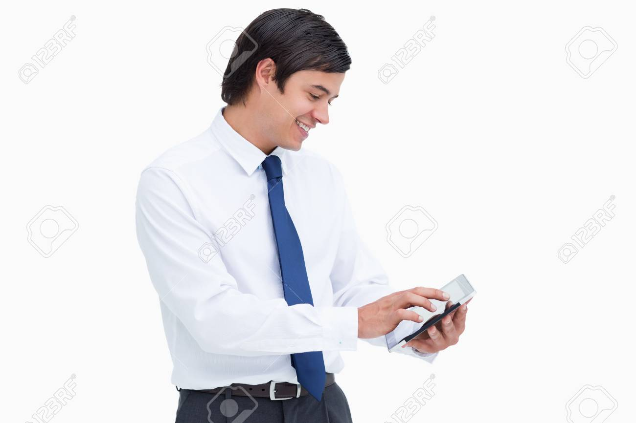 Side view of smiling tradesman using his tablet computer against a white background Stock Photo - 13652567