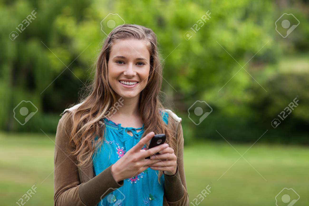 Smiling teenage standing in a park while sending a text with her cellphone Stock Photo - 13668382