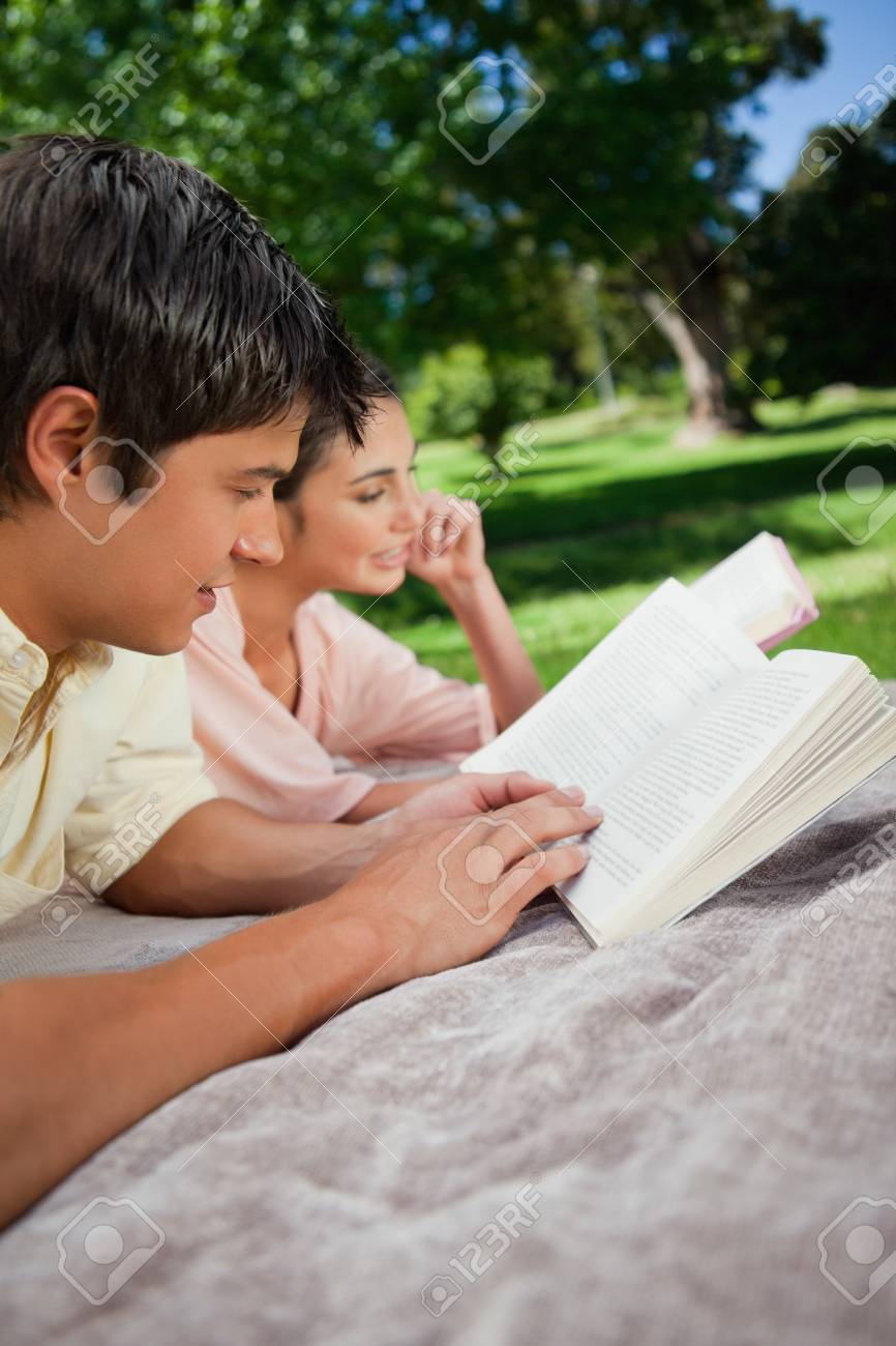 Woman and a man reading books while lying together on a grey blanket int the grass with trees in the background Stock Photo - 13670586