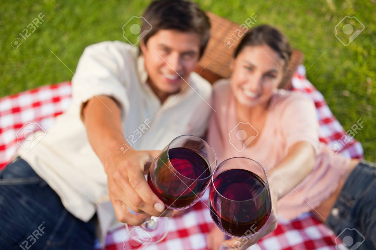 Man and a woman touching their glasses of red while raised during a picnic with focus on the glasses of wine Stock Photo - 13670651