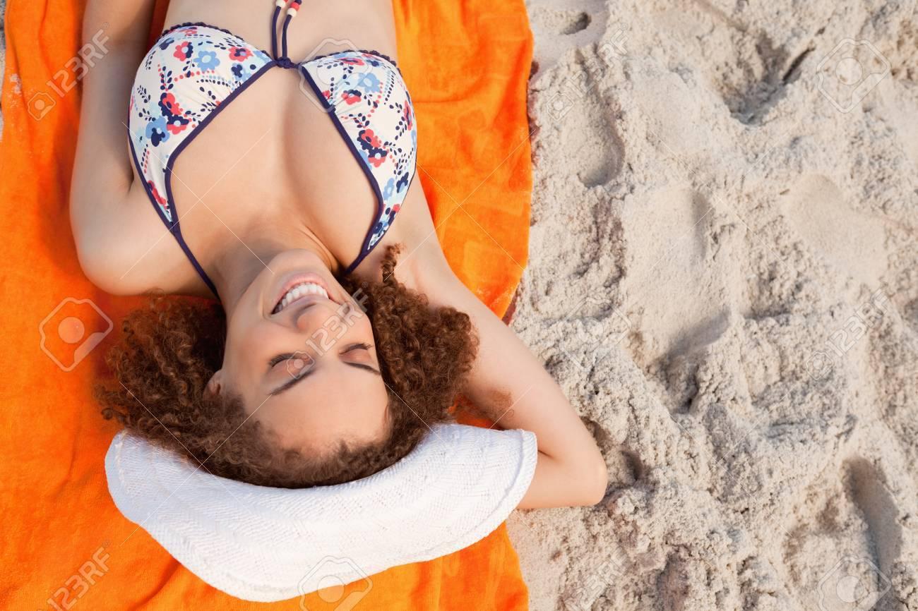4c1fc331a7cb Vista aérea de una mujer joven tomando el sol tumbado en su toalla de playa  de color naranja