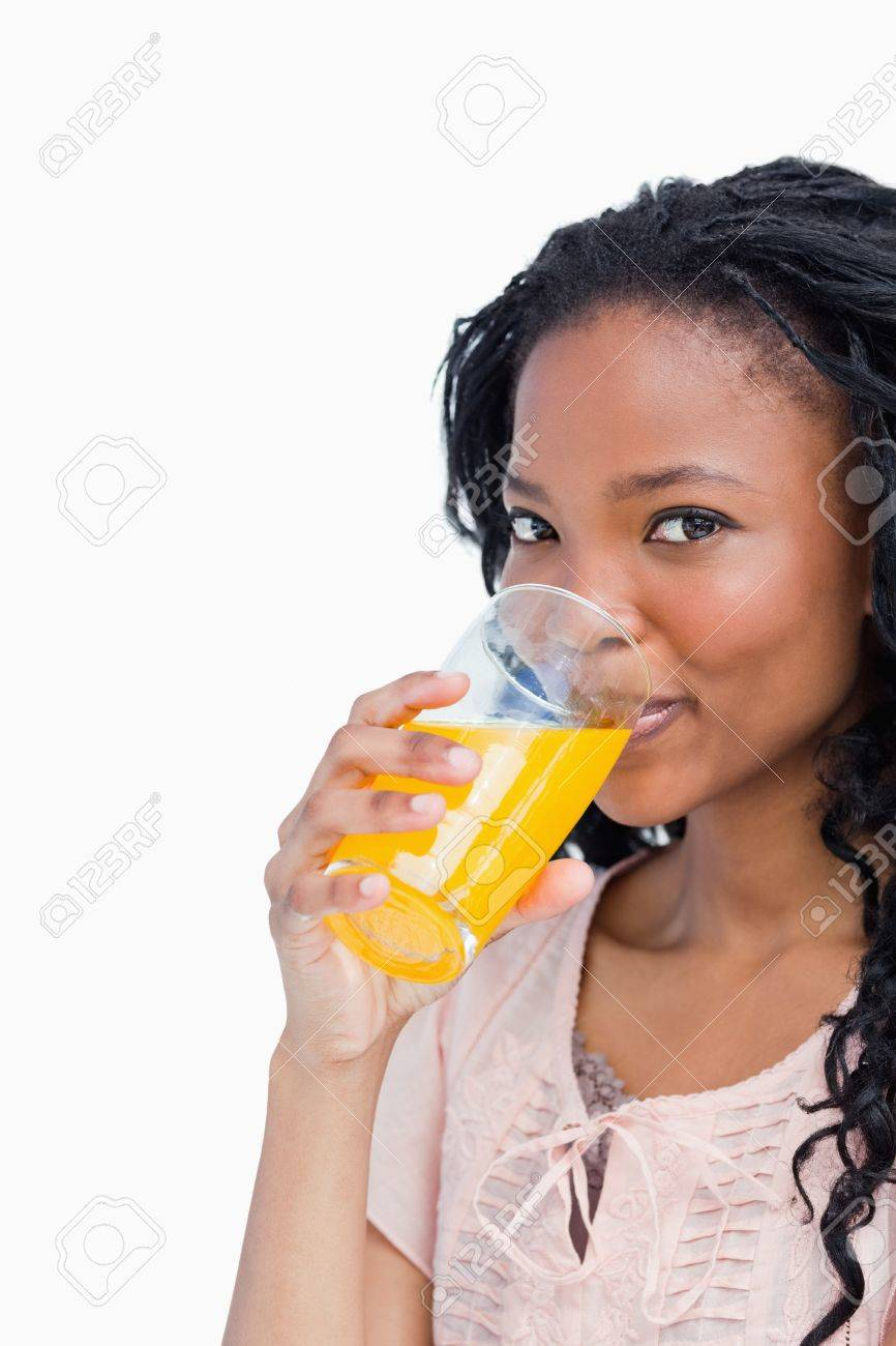 A young girl is looking at the camera and drinking orange juice Stock Photo - 13673104