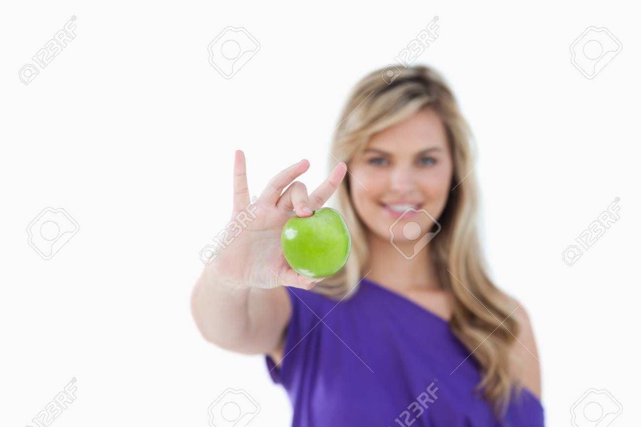 Green apple being held by a blonde woman against a white background Stock Photo - 13674696