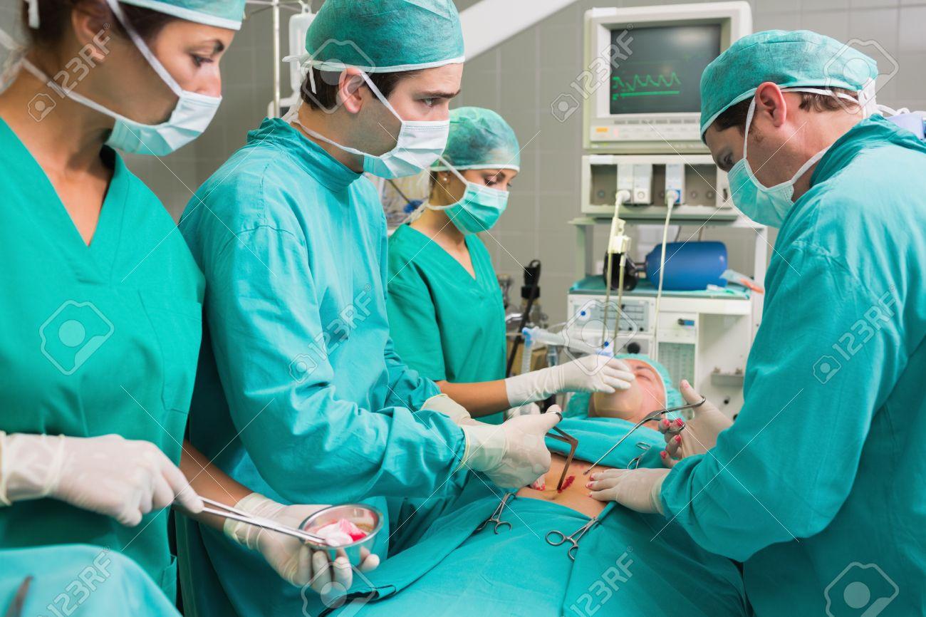 Concentradas Cirujanos Que Operan A Un Paciente En Un Quirófano Fotos,  Retratos, Imágenes Y Fotografía De Archivo Libres De Derecho. Image  15551470.