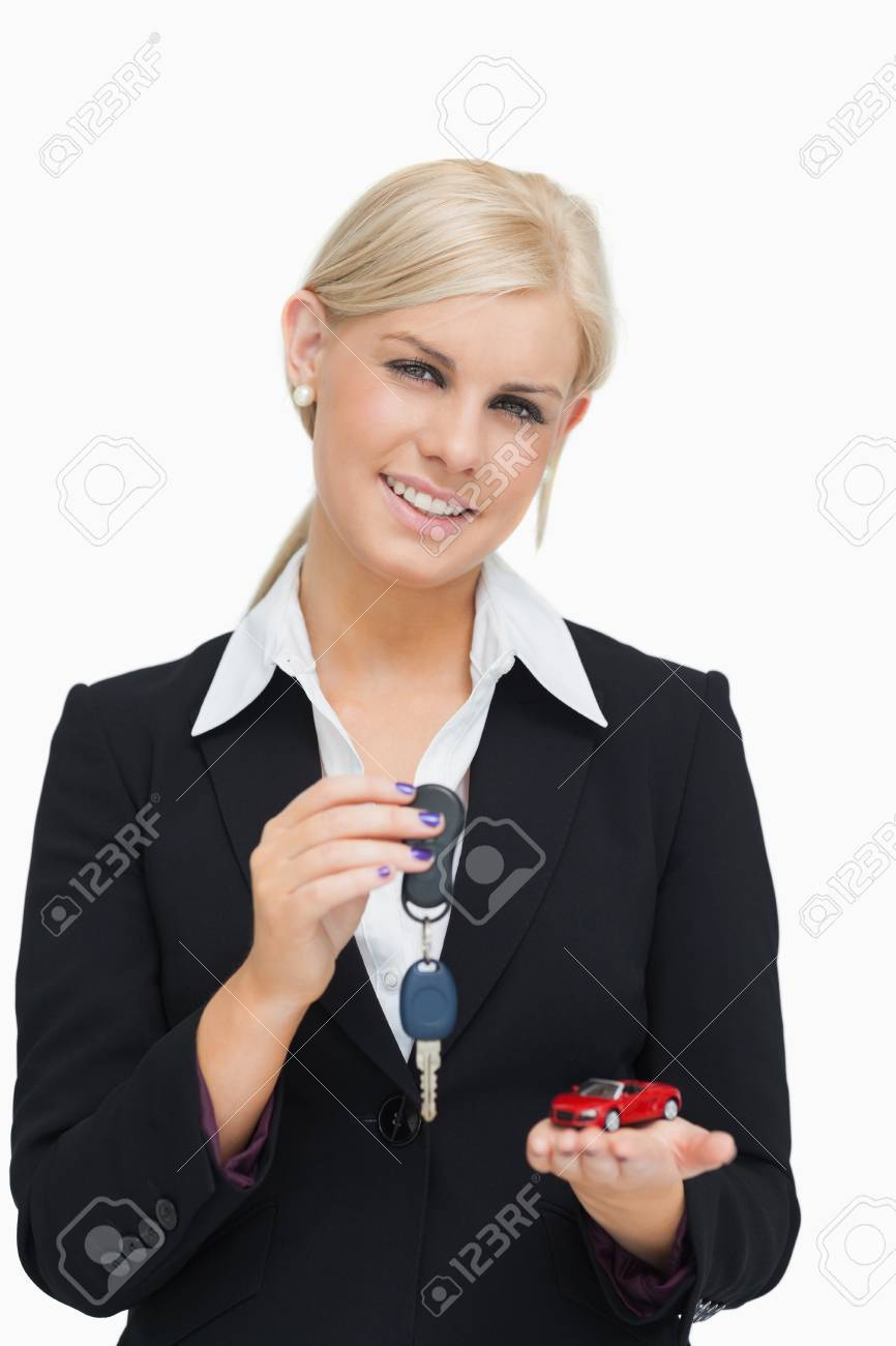 Blonde woman holding key and small car against white background - 15551660