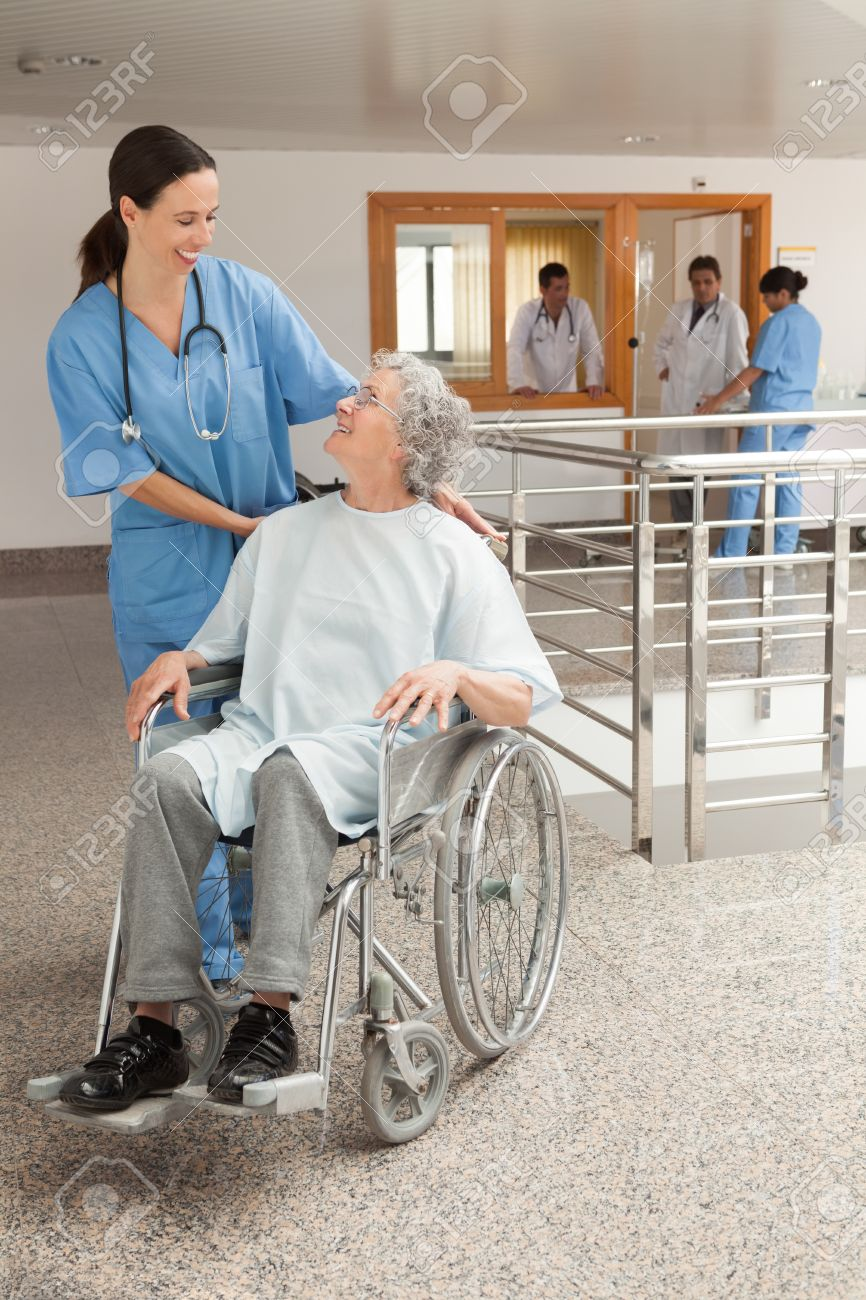 Nurse laughing with old women sitting in wheelchair in hospital corridor Stock Photo - 15584930