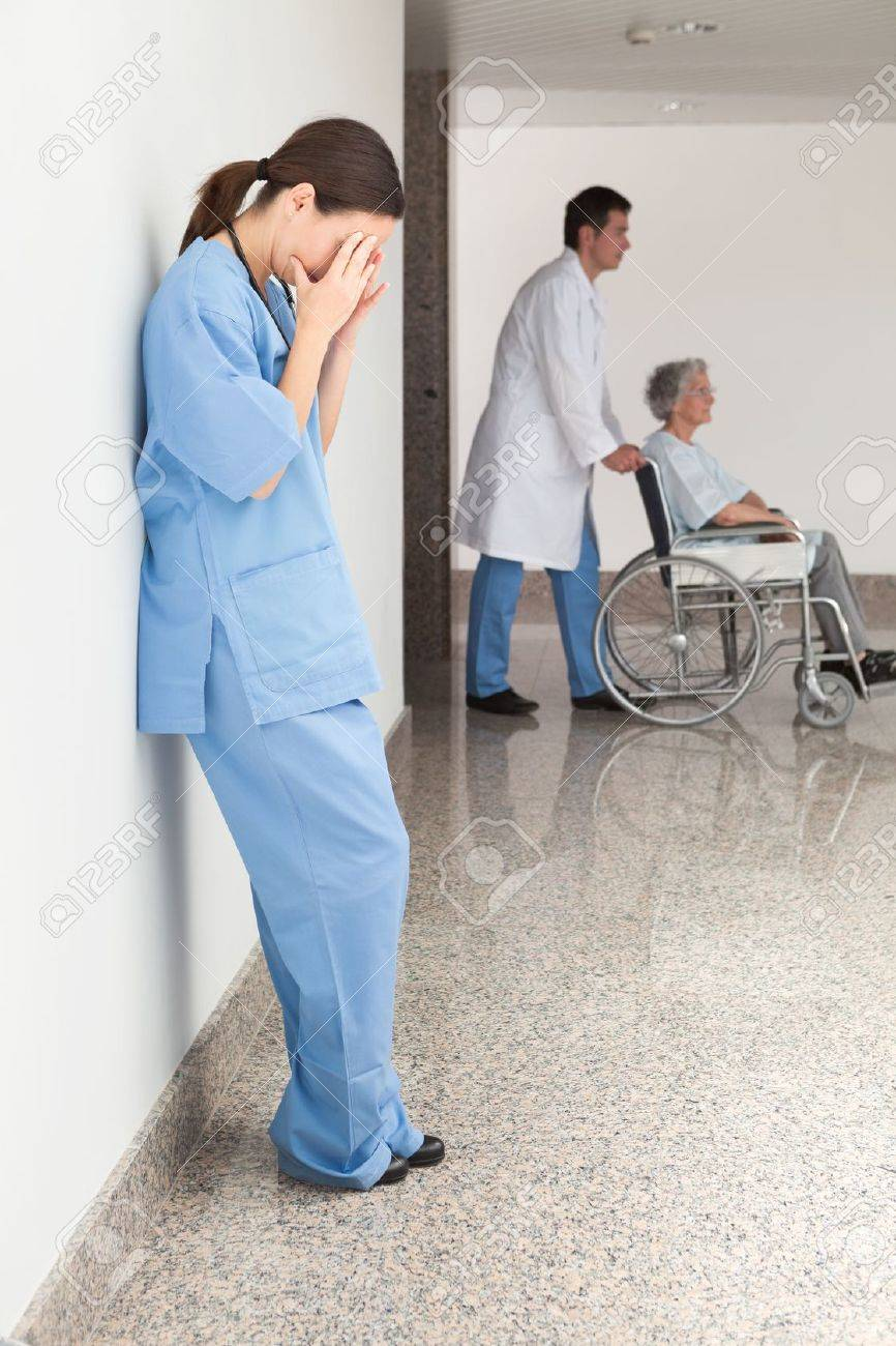 Stressed nurse leaning against wall with doctor pushing patient in wheelchair Stock Photo - 15593129