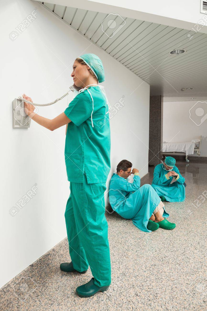 Surgeon using the phone in hospital corridor with two surgeons sitting on floor Stock Photo - 15593161