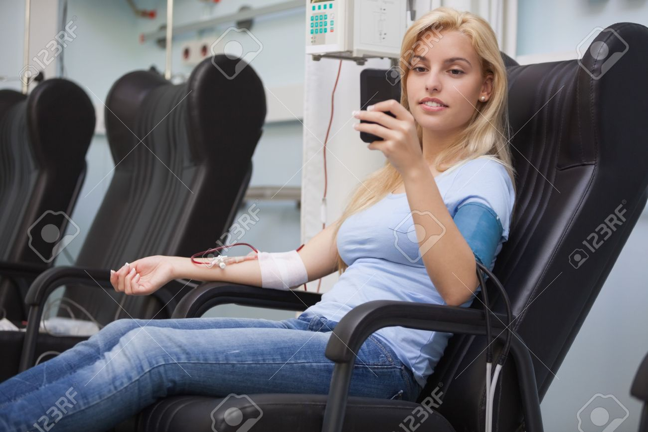 Blonde woman relaxing in a chair while getting dialysis n hospital Stock Photo - 15592540