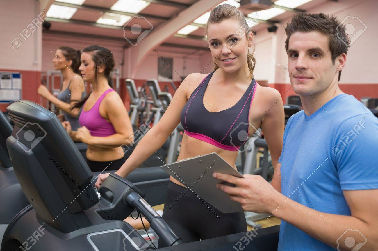 Gym Instructor And Woman In The Gym On The Treadmill Stock Photo ...