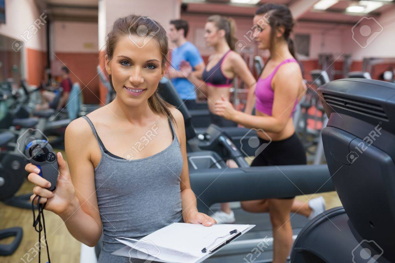 Happy Gym Instructor Showing Stopwatch In The Gym Stock Photo ...