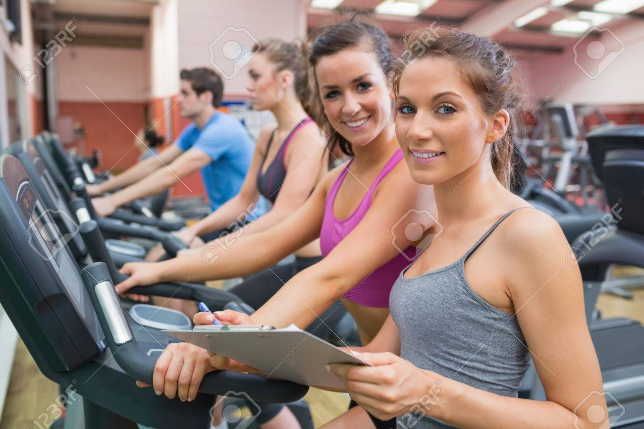 Gym Instructor And Woman In The Gym Smiling On The Exercise ...