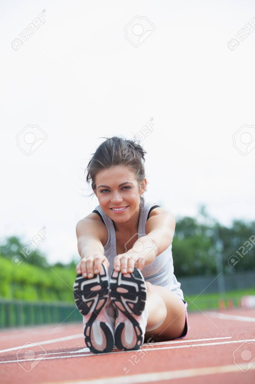 Smiling woman stretching legs on track Stock Photo - 15583484