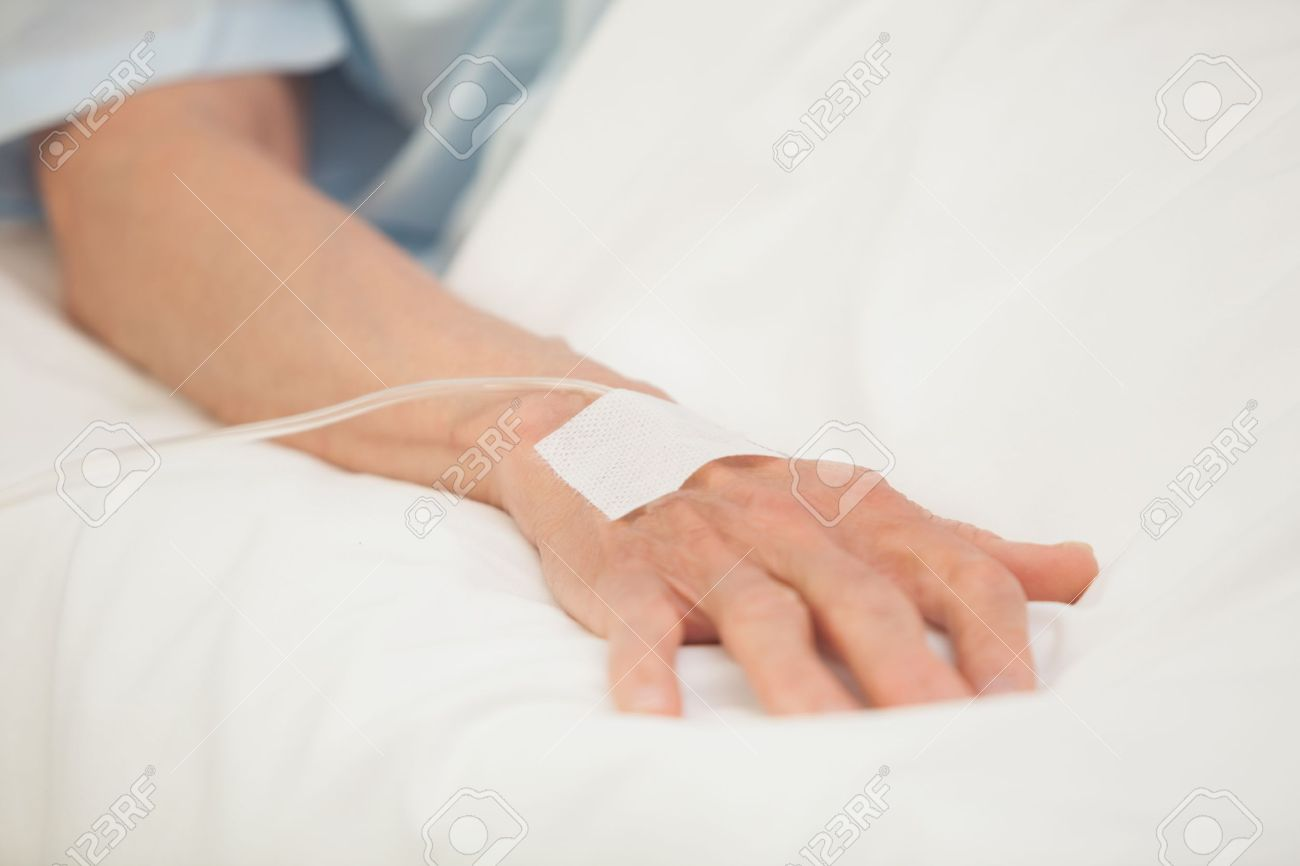 Hand with intravenous drip in hospital bed Stock Photo - 15583304