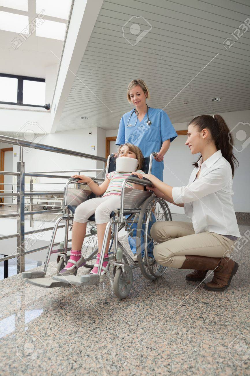 Mother crouches next to her child in wheelchair with nurse pushing it in hospital corridor Stock Photo - 15592859