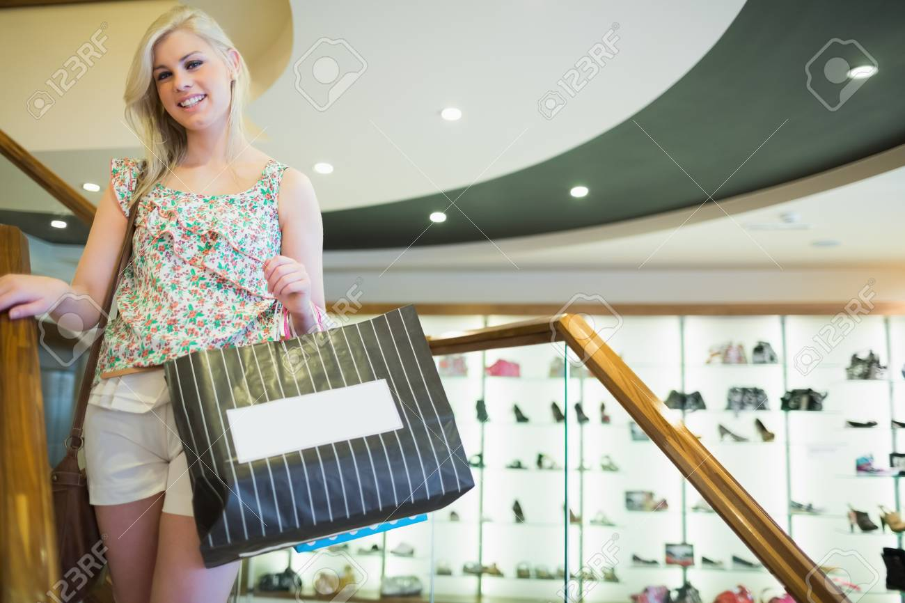 Woman standing on stairs smiling and holding shopping bags Stock Photo - 15593329