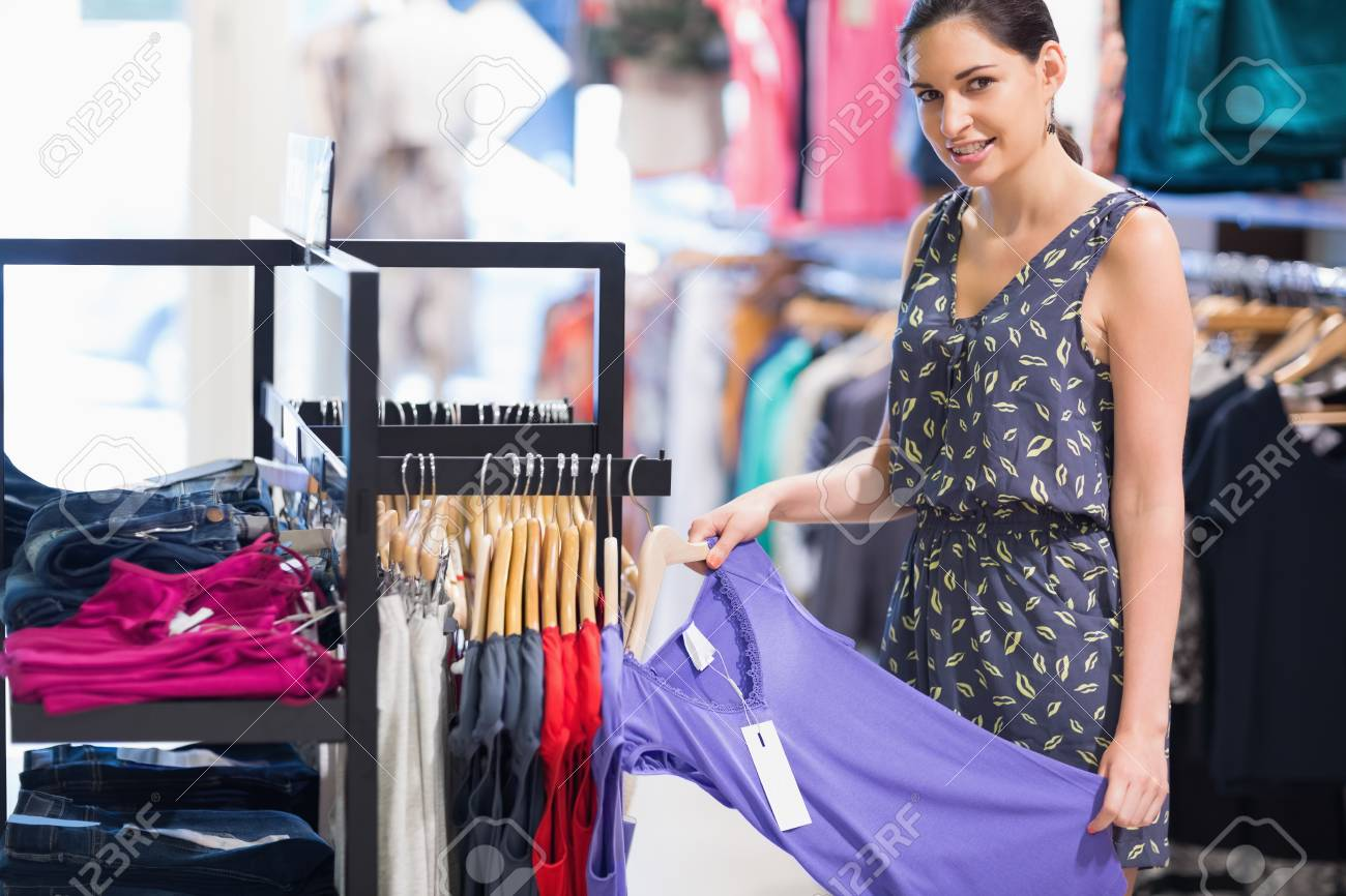 Woman holding purple shirt in clothes store and smiling Stock Photo - 15593162