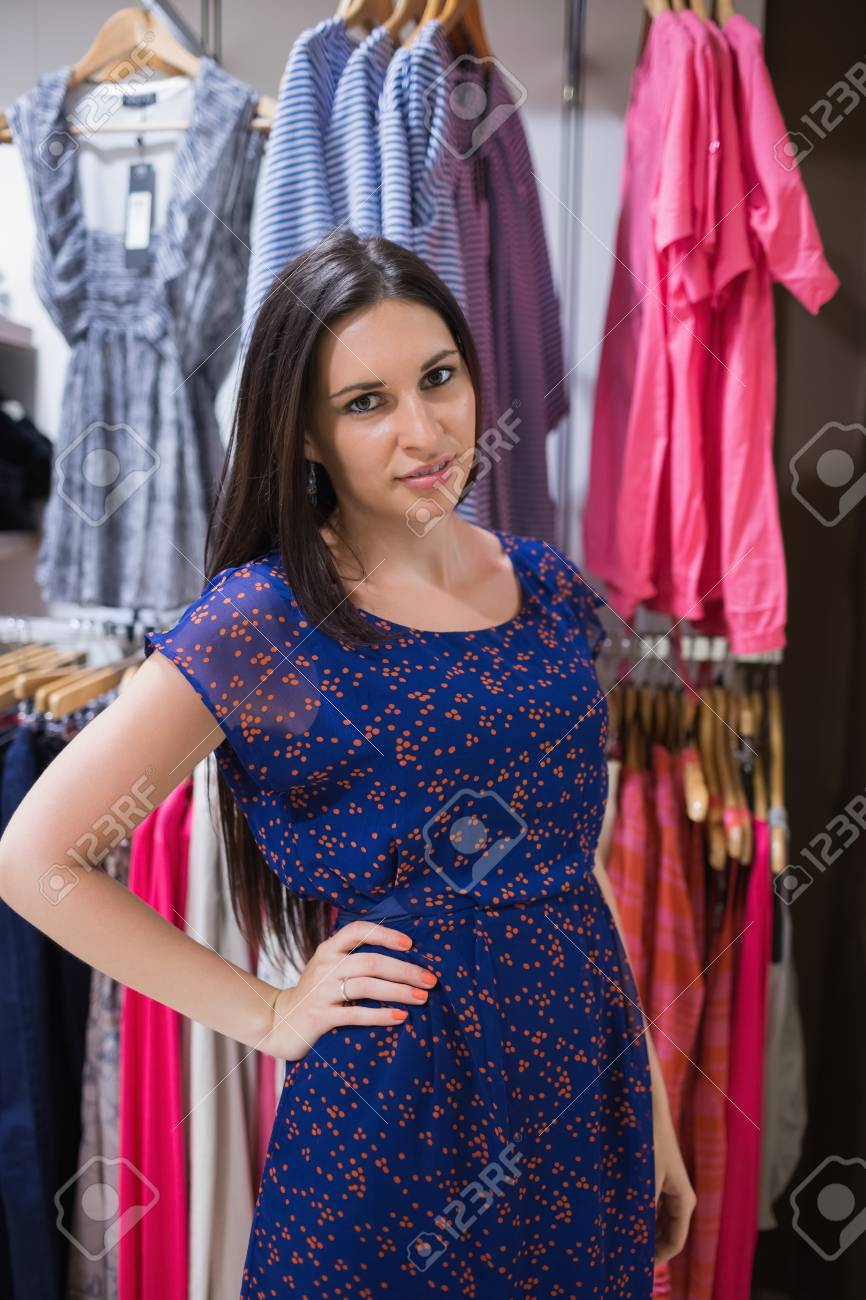 Woman standing in front of clothes rail with hand on hip Stock Photo - 15584953
