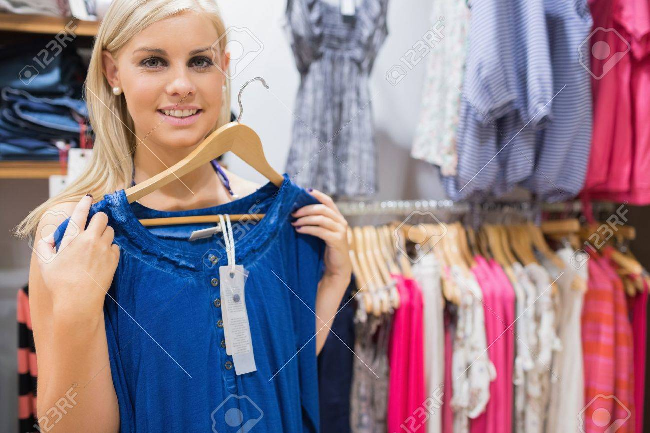 Woman holding up blue shirt and smiling in clothing store Stock Photo - 15585047
