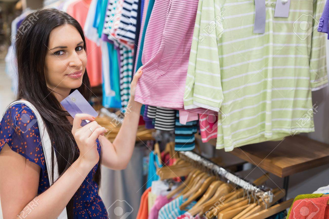 Man Handing Clerk Credit Card In Clothing Store Stock Photo