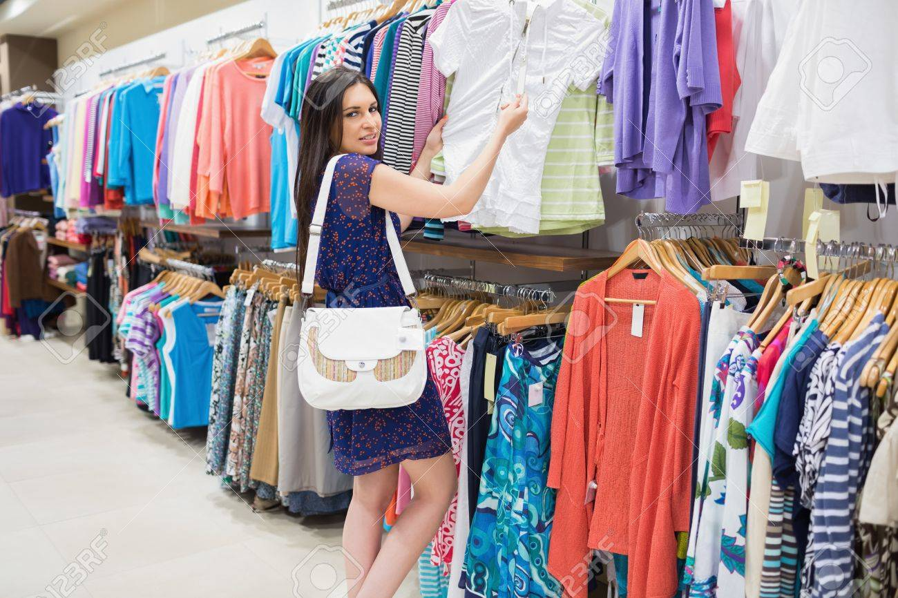 Woman looking at price tag while holding clothes at the shopping mall Stock Photo - 15584293