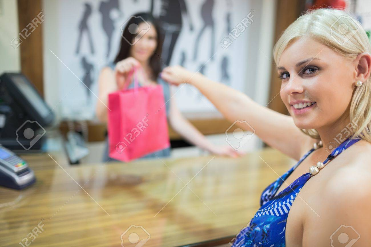 Woman taking bag at cash register in clothing store Stock Photo - 15592813