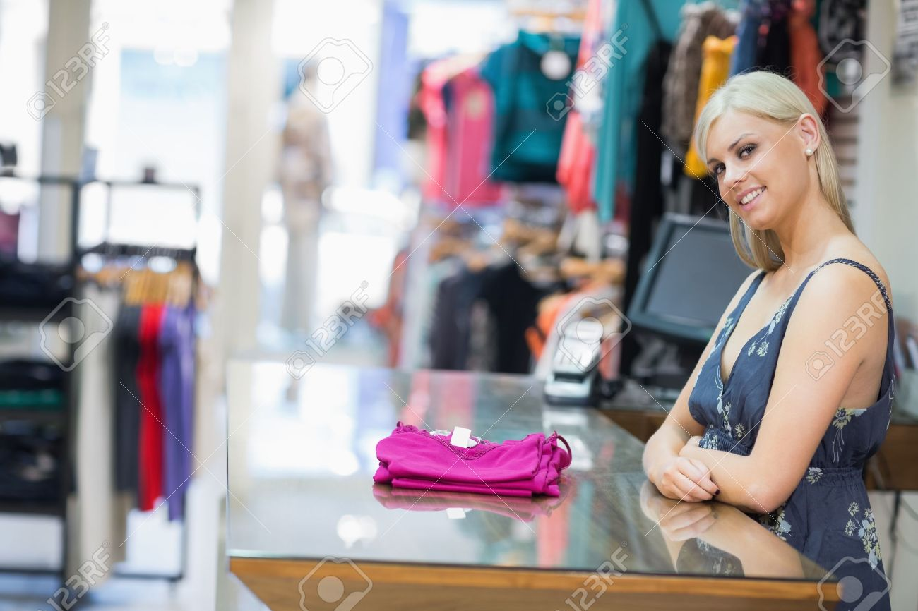 Woman smiling behind counter with folded clothes in clothing store Stock Photo - 15592576