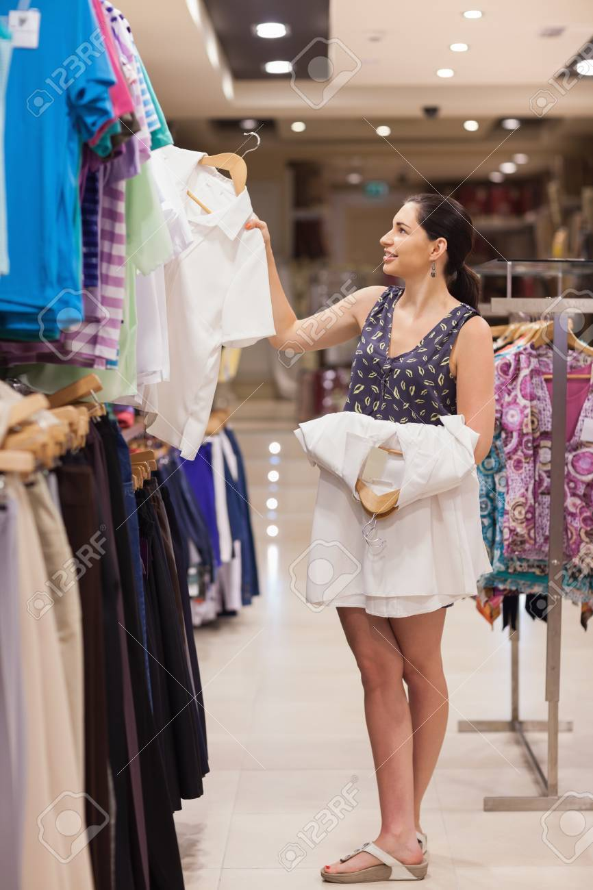 Woman holding white shirts on hangers in clothing store Stock Photo - 15591647