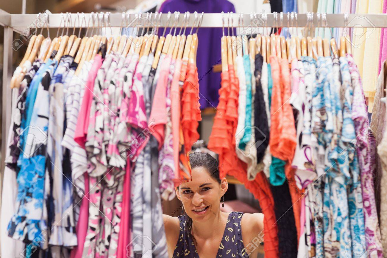 Woman standing behind a clothes rack of a store smiling Stock Photo - 15592824