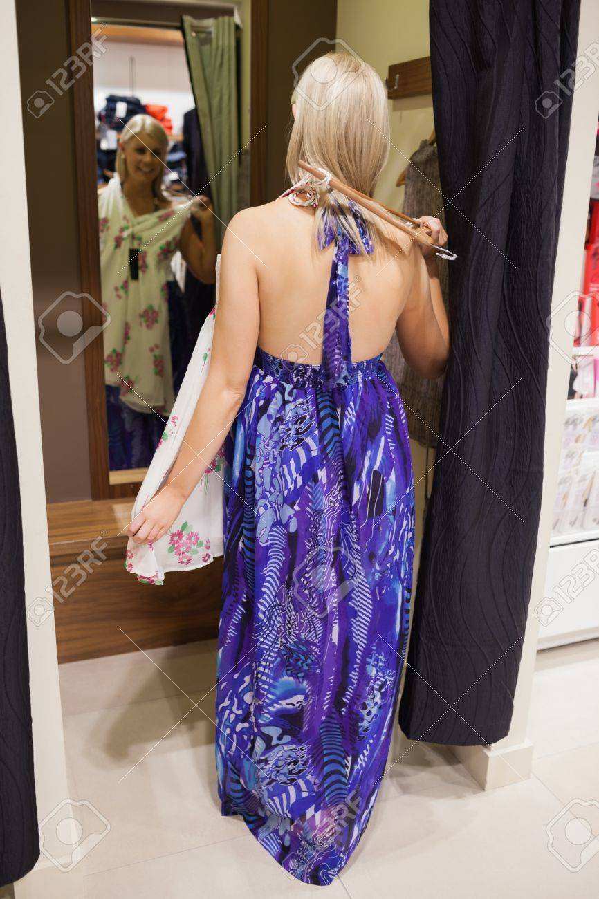 Woman standing in the changing room of a store trying clothes Stock Photo - 15592287