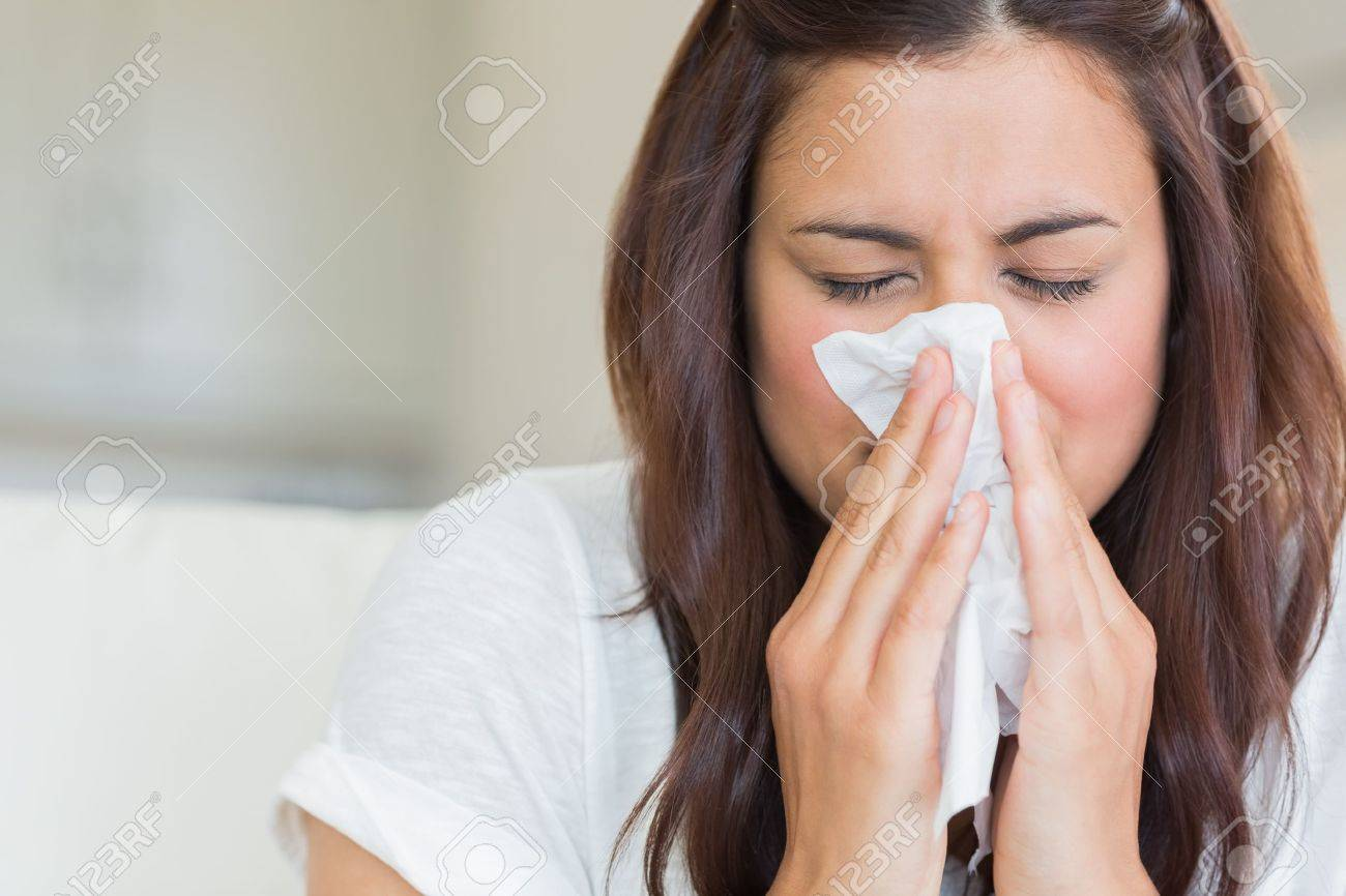 Burnette woman blowing nose into tissue Stock Photo - 15591466