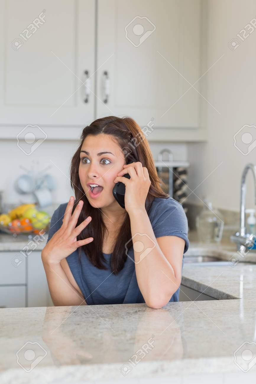 Surprised woman on phone in kitchen Stock Photo - 15591191