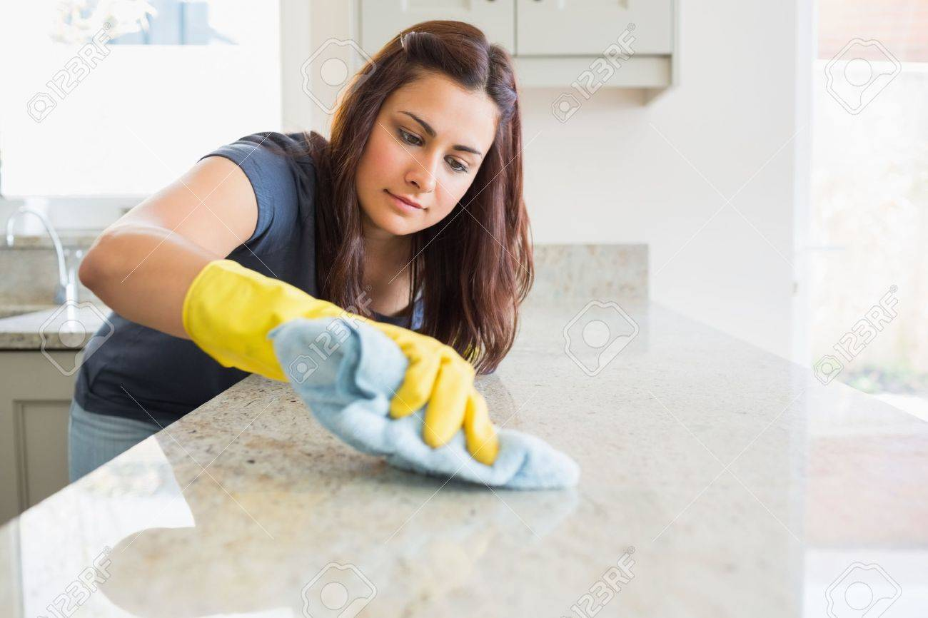 Concentrated woman scrubbing the bar in kitchen - 15589920