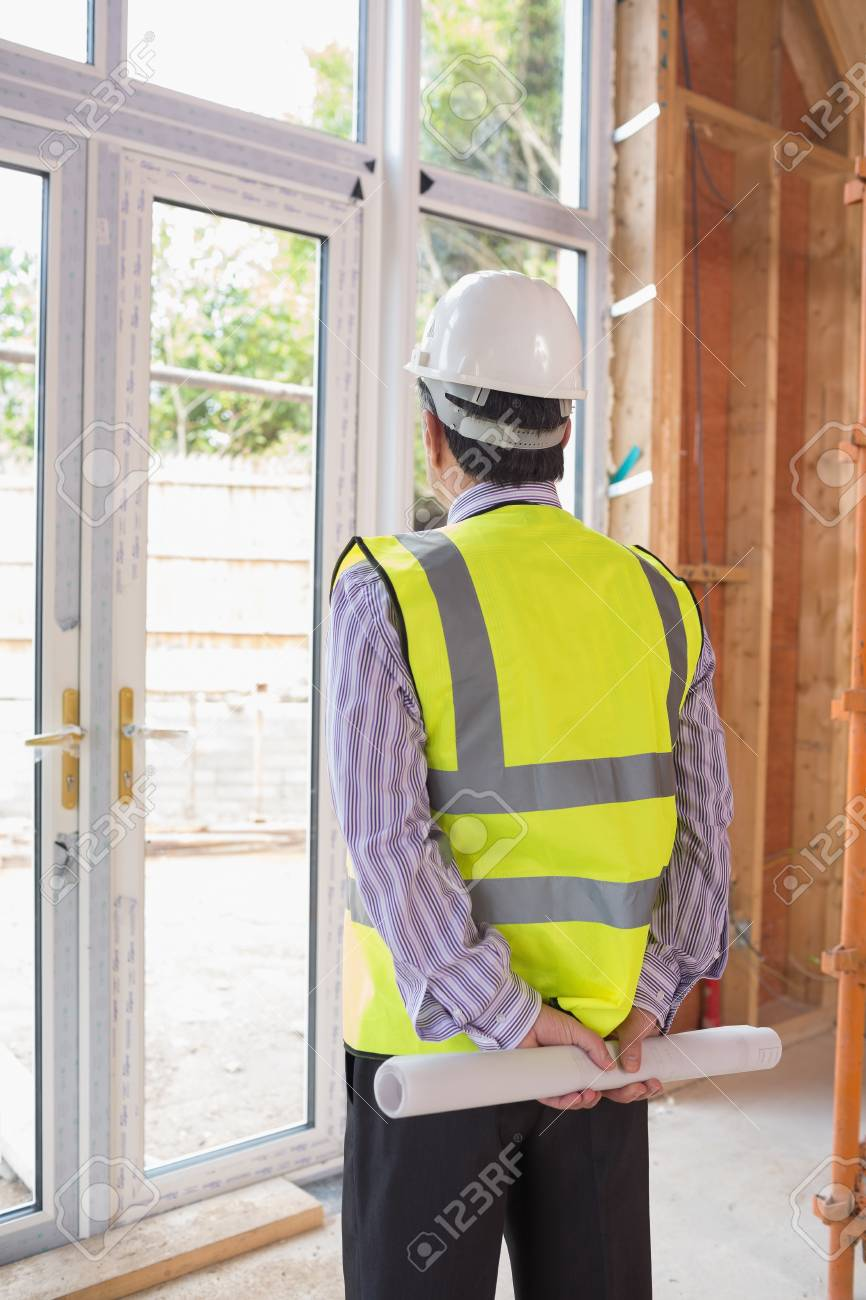 Architect wearing a warning vest and a helmet looking out of the window Stock Photo - 15593323