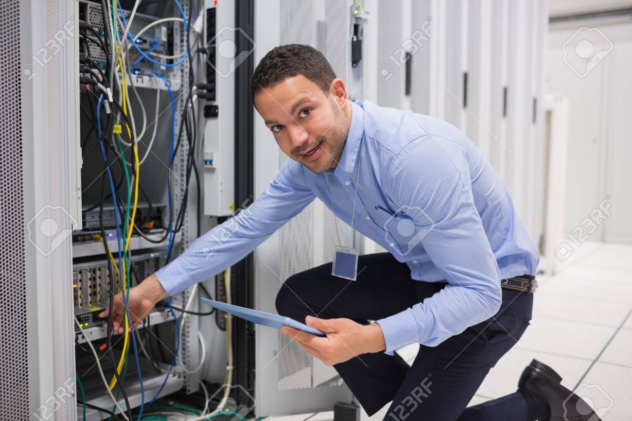 Smiling Technician With Tablet Pc Plugging Cables Into Server ...