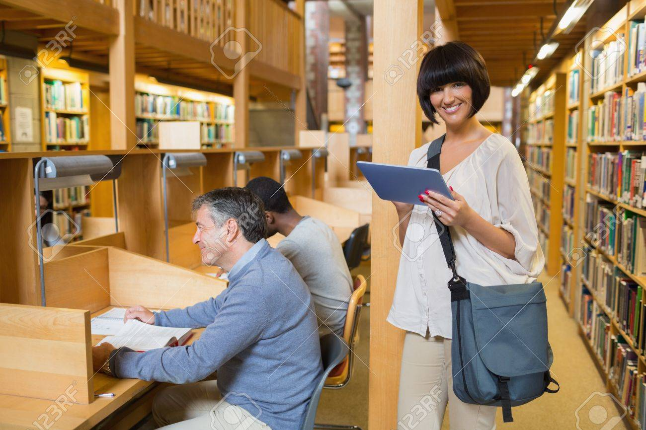 Woman smiling and holding a tablet pc  with other people reading in the library Stock Photo - 15584437